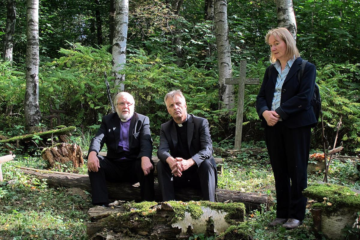 Visiting Keltto cemetery near St Petersburg: (left to right) ELCIR Bishop Arri Kugappi, LWF General Secretary Rev. Martin Junge and Europe Area Secretary Rev. Dr Eva Sibylle Vogel-Mfato at Keltto cemetery, a safe worship space for Ingrian Christians during Communist rule. Photo: Pekka Mikkola/FELM