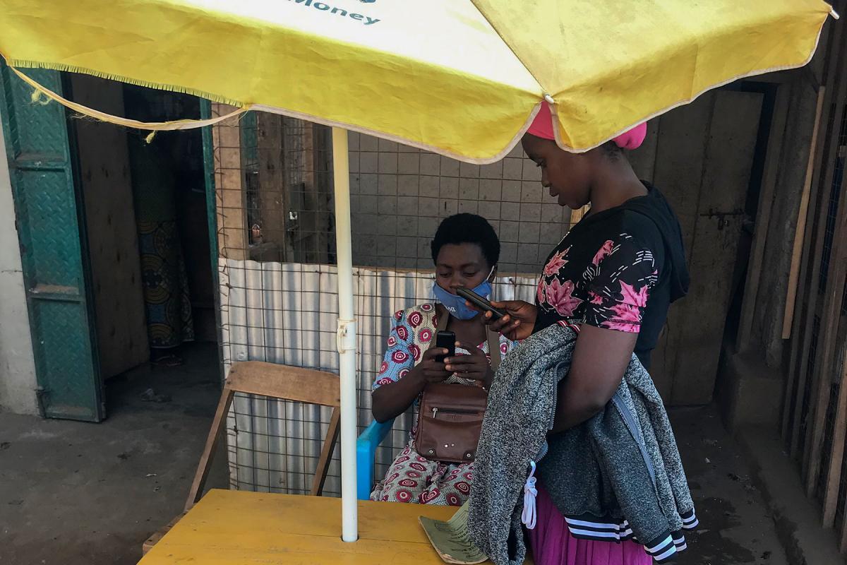 Vestina attending to a customer at her mobile money business in Kyangwali refugee settlement. Photo: LWF Uganda