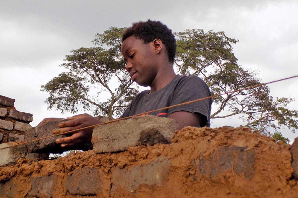 Hawa Andrew constructs a wall. Photo: LWF/ S. Nalubega