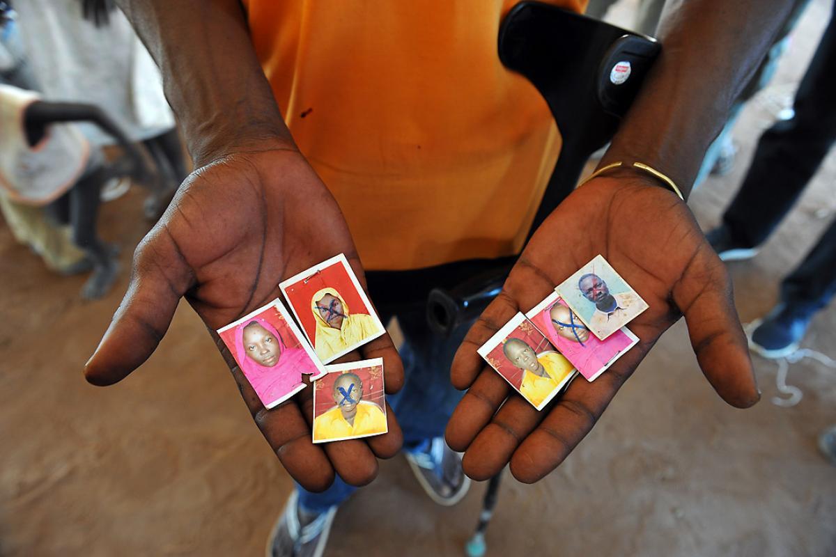 A refugee hold images of family members killed in the South Sudan conflict, Njumanzi reception center, Adjumani, Uganda. Photo: LWF/ M. Renaux