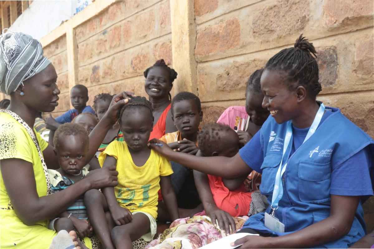 Sarah Ewoi, with a South Sudanese refugee family at Nadapal center. Photo : LWF Kenya