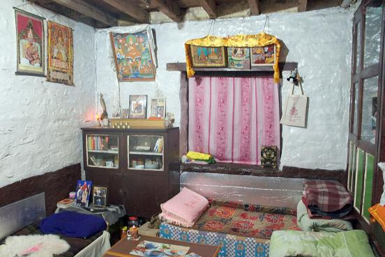Tashi's small living room shows paintings and photos of the 14 Dalai ...